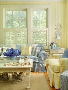 Pastels Grow Up - A pastel palette rich in yellow and blue humanizes the large scale of this living room and imparts a cottage vibe. Walls are painted in a pale yellow to let accents and furnishings pop. The blues veer toward sea blue rather than baby blue to avoid an overly sweet color palette. Stylish plaid and striped fabrics on tailored furnishings lend a grown-up, elegant tone to the pastel scheme.