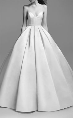 ball gown silhouette with a low cut neckline, Spaghetti straps Embellished waist band fitted bodice and pleated skirt.