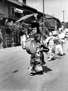 A Japanese man in costume beats the drum as he leads a musical parade of men and women who are walking advertisements featuring placards for restaurants through the streets of Tokyo, Japan, Feb. 14, 1947. (AP Photo) Ref #: PA.8661110