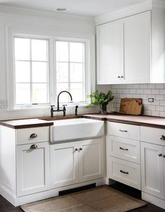 Gorgeous cottage kitchen boasts white shaker cabinets fitted with dark nickel vintage cup pulls and dark butcher block countertops holding a farmhouse sink accented with a bronze deck mount gooseneck faucet sat in front of a window.