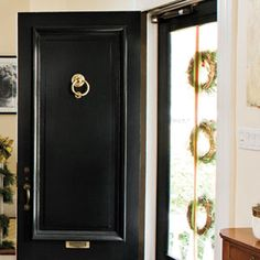 Hang Three Wreaths    Forgo the traditional single wreath on a front door and welcome Christmas guests instead with three miniature wreaths. Attached to a long piece of ribbon, the smaller wreaths are ideal for a glass-front door.
