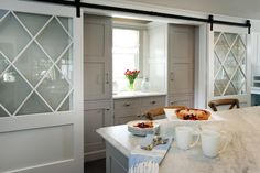 pair of sliding barn doors with glass panels on rails open to butler's pantry f