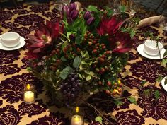 Italian inspired centerpiece decor rich in shades of plum atop a tapestry inspired linen. www.konceptevents.com