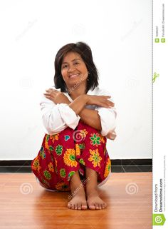 Portrait of a happy smiling young Asian woman sitting on the floor