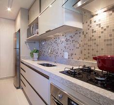 Cozinha com bancada em granito, parede com pastilha de vidro e armários superiores em vidro…