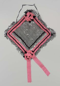 Cap; square, of black dotted net; trimmed on edges with pleated bright pink silk ribbon with narrow black velvet ribbon holding pleated ribbon in position; rosettes, of pink ribbon and black velvet ribbon, on two diagonally opposite corners; double flounce of narrow bobbin lace around outer edges; narrow black elastic attached to front point; designed to be worn around bun of hair.