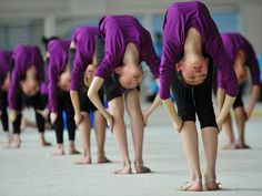 Students stretch during a training session at a gymnastic course at Shenyang Sports School