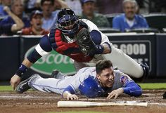 New York Mets' Wilmer Flores, bottom, is tagged out at home plate by Atlanta…