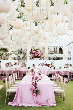Linternas de papel y flores suspendidas como centros de mesa colgantes en esta boda en blanco y rosa.