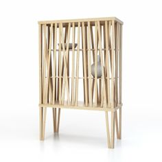 An open structure of Olive Ash wood sticks makes creates a transparent piece, somewhere between a vitrine and a cupboard.
