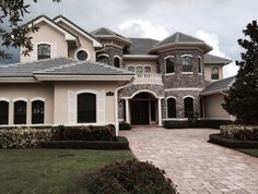 Beautiful estate in boynton beach, fl,that combines rustic stones with balconies ,earth color paints for the exterior walls, dark brown wood entrance and garage doors, roman columns, that create a luxury look in this equestrian community.