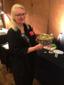 Antique dealer Carol Hageness of Sunshine Treasures holds an 8 1/2-inch repousse style sterling bowl with gold wash, circa 1860s, that carries a price tag of $2,250. Photo by Karen Knapstein.