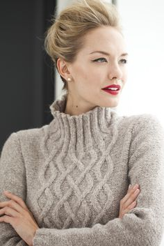 "A split climbing cable, mirrored on the back, complements the contours of Melissa Leapman's bell-shaped pullover. Reverse stockinette texturizes the background and sleeves; the cable flows into the ribbed mock turtleneck, which is picked up and knit in finishing. It's knit in Berroco's ""Voyage,"" a heathered chainette, to create a soft yet structured fabric."