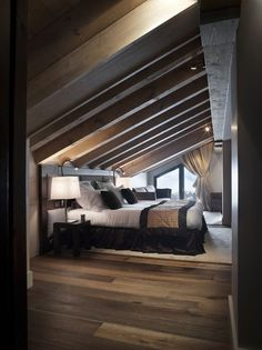 Masculine attic master bedroom with dark wood beamed sloped ceiling, dark wood floors and large bed.