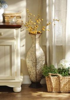 Add this metal floor vase to any room for a bold, stylish look! With its distressed cream finish and metal construction, this durable floor vase goes with any decor.