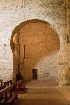 Interior de San Miquel de Cuixà (Rosselló), se aprecia uno de los arcos de herradura que permite ver la tradición prerrománica mozárabe. La girola , después de un incendio, el Abad Oliba la hizo reconstruir. Se edificó una cabecera plana en lugar de semicircular también herencia de las construcciones anteriores.