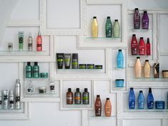 Products making a colourful splash against a white wall at Facto Royale Salon in Lisbon