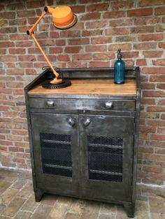 Ancien meuble industriel d'usine, d'atelier, en patine graphite , 2 portes grillagées, un grand tiroir avec des poignées coquilles, et un dessus bois. A l' intérieur il se compose d' une large étagère. Style : Mobilier Industriel