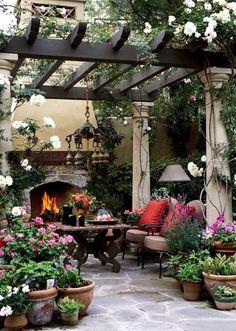 Grandes pérgolas idea de diseño con columnas de piedra y techo de madera, rodeada de flores, enredaderas, hierbas.