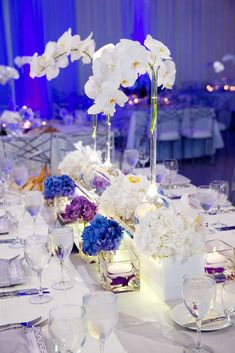 Reception tables were topped with arrangements of hydrangeas in white, blue, and purple hues, as well as towering long-neck vases filled with ivory phalaenopsis orchids. #tabledecor #weddingreception Photography: Bob & Dawn Davis Photography. Read More: https://www.insideweddings.com/weddings/modern-purple-blue-white-wedding-at-contemporary-chicago-venue/541/