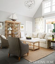A muted palette with a jute rug and rattan chairs establishes an elegant, airy ambience in the pool house living room. - Photo: Werner Straube / Design: Robert Bakes