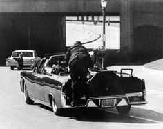 """President John F. Kennedy slumps down in the backseat of his presidential limousine in Dallas after being fatally shot by a sniper. First lady Jacqueline Kennedy leans over the president as Secret Service agent Clint Hill pushes her back to her seat. """"She's going to go flying off the back of the car,"""" Hill thought as he tried to secure the first lady."""