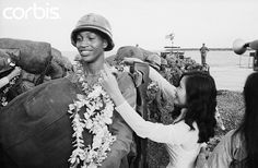 A young Vietnamese girl presents a floral wreath to an African American soldier arriving with the 25th division on January 18, 1966 at Vung, Tau, forty miles south of Saigon. --- Image by © Bettmann/CORBIS