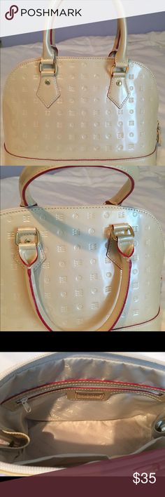 """Acadia- vanilla patent leather bag Perfect for spring and summer! Vanilla-colored Acadia patent leather bag with red piping on handles. Slight discoloration on one side of the bag, along the bottom- shown in 4th picture. Looks like light pink marks. Inside of bag is immaculate- I only used it twice! Discoloration is probably from rubbing against another bag in my closet. Measures: 12"""" wide, 8"""" tall, 5.5"""" wide base. Handle drop 4"""". Reasonable offers, no trades. Smoke- and pet-free home…"""