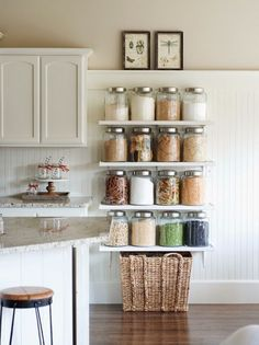 Running out of space in your pantry? Use glass jars on wall-mounted shelves to attractively display dry goods. (Just make sure those shelves are secured to the wall real good.)