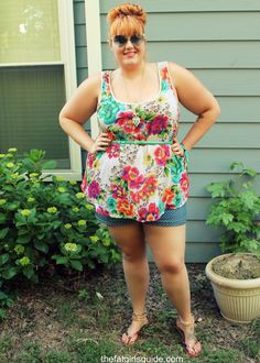 Plus size jean shorts from Torrid! Floral top, top knot, and colorful sandals and a mint skinny belt to finish the look.