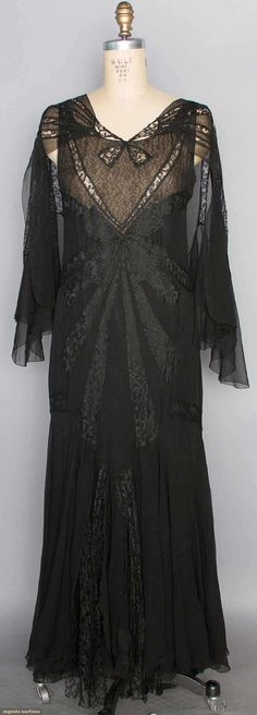 """CHANEL CHANTILLY LACE GOWN, 1930s Black silk chiffon full length bias-cut gown w/ lace insertions in bow & ribbon patterns, low V back, shoulder capelet, narrow chiffon & lace streamers attached to sides by hips & at CB, lined in black silk charmeuse w/ deep lace flounce, brown on cream woven label """"Chanel"""" & stamped linen tape """"96196"""", B 36"""", W 30"""", L 53"""", (2"""" tear in insertion lace at right shoulder)"""