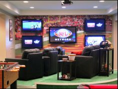 Game room/man cave chair and tv set up also foosball table but now wallpaper behind tvs, just wood
