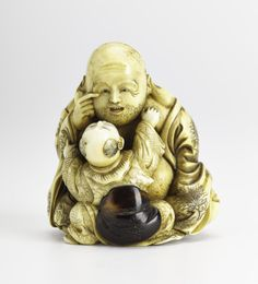 Netsuke of carved ivory, Hotei? sitting holding a finger to his right eye at which a child gazes, behind him is a small green mask held by string, signed: Japan, 19th century