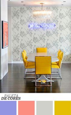 Floral com personalidade: as estampas florais costumam ser usadas, na maioria das vezes, em ambientes tradicionais e românticos. A padronagem surge nessa sala de jantar em tons de cinza, cor que funciona muito bem com a ousadia das cadeiras amarelas e do néon da parede. Que tal? Clique na foto para ver mais