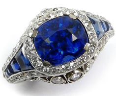 Art Deco sapphire and diamond ring, circa 1925. Via Diamonds in the Library. 3.81cts cushion-cut Burmese sapphire and tapering calibre cut sapphire shoulders, all bordered by diamonds. It has graduated collet set diamonds to the cagework gallery, a reeded shank, and is mounted in platinum mounted.