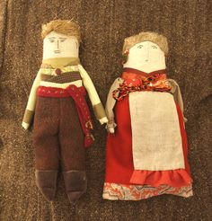 Vintage Russian Folk Art Dolls, circa 1960s. The woman is wearing a sarafan, the traditional sleeveless dress, or skirt with a bodice stitched to it. common in many regions of Russia in the late 19th and early 20th centuries. Her body is cloth, hair is of wool, and her earrings are 5 Kopek coins.  The man's body is cloth, his hair is made of straw. He is wearing traditional flyless porty,(pants), with a sash. Each doll measures 10 1/2 inches tall.
