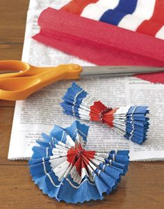 "1 From blue crepe paper, cut a strip 8"" wide & 20"" long.  #2 Cut a narrower strip of newspaper. Lay it down in the center of the blue strip, gluing in place. Repeat, cutting an even narrower strip of red crepe paper, then gluing in place. #3 Fan-fold across the narrow width of the strip. Fold in half lengthwise....."