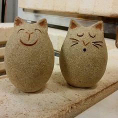 Kaksi keramiikka kissaa.