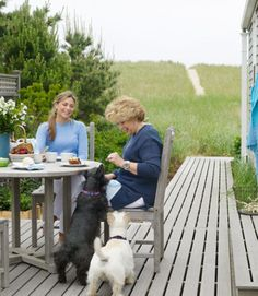 Homeowner Linda and her daughter Lily—and their Scottish terriers Mack (left) and Maisie—eat breakfast on their Nantucket cottage's deck.