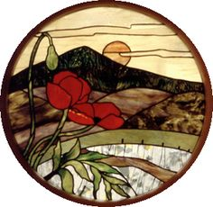 This photo is of a circular stained glass window depicting a poppy with hills and the sun in the background