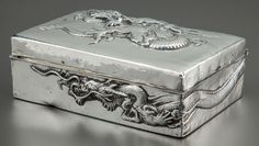 A beautiful silver box of Chinese origin with an undulating dragon-from on a hinged lid with another dragon wrapping the sides. Wood-lined, circa 1900.