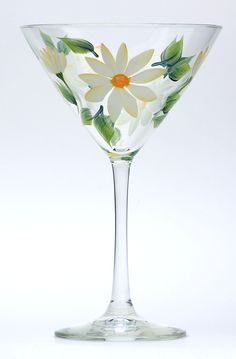 Daisies of creamy white with yellow highlights, yellow centers and green leaves encircling a high quality 12 ounce martini glass