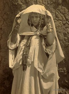 """The Ouled Nail (""""will-ed nah-eel"""") was a Berber tribe of the Atlas Mountains of Algeria. The women (Nailiyat) in adolescence went down into cities unescorted by men, worked for a time as dancers + prostitutes to amass a personal fortune to purchase property at home, after they'd done this they'd marry. Typical Nailiyat knew nothing of sexual shame. The Nailiyat danced erotically (sometimes w/o clothes). To learn more follow the link."""