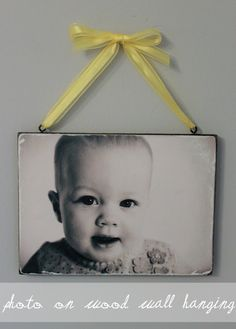 Just print off any picture, spray paint a piece of wood black, cut the picture to match the size of the wood. Coat the wood with Mod Podge and lay the picture on top. Once it has dried thoroughly, use sandpaper to rough up the edges, then seal the photo with another layer of Mod Podge.  Screw-in and paint eye hooks and hang with a pretty ribbon. Voila!