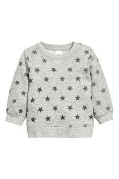 Sweater met print: CONSCIOUS. Een sweater van zachte joggingstof van biologisch katoen met een zachte, geruwde binnenkant en een geprint dessin. De sweater heeft een drukknoopsluiting op een van de schouders en een ribboord bij de hals, aan de onderkant en onder aan de mouwen.