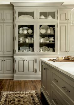Gorgeous gray kitchen boasts gray kitchen island topped with white marble countertop facing a wall of floor to ceiling gray cabinets flanking a built-in gray china cabinet with glass doors.