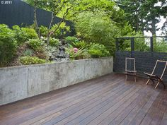 Backyard deck/patio, black fence, poured concrete retaining wall.  @ 5641 SW MENEFEE Dr  Portland, OR 97239