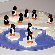 Cream cheese black olive penguins (love the way they're placed on floating ice) *the cream cheese also makes it less troublesome to keep them standing upright...I highly recommend you do the cream cheese (even if you just spread it out on the plate like snow instead of ice)