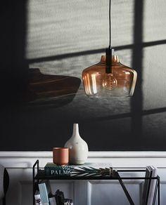 Kyoto er en liten serie svært elegante taklamper i behandlet glass fra Frandsen. Denne pendelen har en stor, klar skjerm som er delvis dyppet i bronse, Bronze Dip Dyed, noe som gir den et meget vakkert uttrykk. Lampen har sort sokkel, takkopp og sort tekstilledning.
