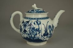 "Teapot and lid; porcelain; globular body; thick neck rim; curved spout; faintly ribbed handle; lid with brim and flower knop; both teapot and lid painted with ""The Bird in a Ring"" pattern and border pattern in underglaze-blue with oriental flowering shrub, bird in cage and pot of tall leaves on table; spout and handle painted in underglaze-blue; deep footrim; mark (on teapot)."